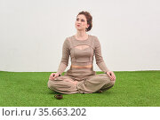 Young woman sitting in meditation pose and looks up dreamily on light background. Стоковое фото, фотограф Евгений Харитонов / Фотобанк Лори
