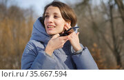 Young woman with wireless headphone is using her smartphone to send a voice message to a new social network Clubhouse standing somewhere outdoors at the park. Стоковое фото, фотограф Ольга Балынская / Фотобанк Лори