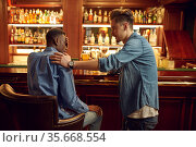 Male friends drinks beer at the counter in bar. Стоковое фото, фотограф Tryapitsyn Sergiy / Фотобанк Лори
