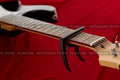 Electric guitar fretboard with capodaster, closeup