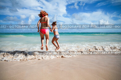 Girls jump in shore waves on a sunny day