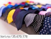 row of Neckties on hangers in men clothing store. Стоковое фото, фотограф Татьяна Яцевич / Фотобанк Лори