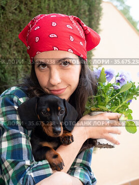 Beautiful Young woman gardening at home planting flowers in pots ...