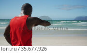 African american man checking his smartwatch, taking break in exercise outdoors by the sea. Стоковое видео, агентство Wavebreak Media / Фотобанк Лори