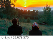 man and woman hikers sit on the mountainside in sun loungers and meet the dawn. Стоковое фото, фотограф Акиньшин Владимир / Фотобанк Лори