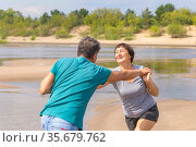 beautiful mature sportive couple doing gymnastic exercises on the beach on a summer day. Стоковое фото, фотограф Акиньшин Владимир / Фотобанк Лори