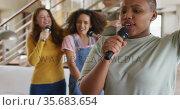 Diverse group of female friends having fun singing karaoke at home. Стоковое видео, агентство Wavebreak Media / Фотобанк Лори