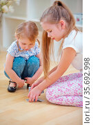 Zwei Kinder mischen Karten vor dem Spielen auf dem Boden. Стоковое фото, фотограф Zoonar.com/Robert Kneschke / age Fotostock / Фотобанк Лори