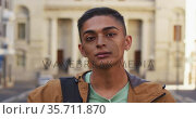 Mixed race man looking at camera and smiling in the street. Стоковое видео, агентство Wavebreak Media / Фотобанк Лори