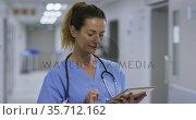 Thougtful caucasian female health worker using digital tablet in the corridor at hospital. Стоковое видео, агентство Wavebreak Media / Фотобанк Лори