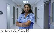 Portrait of smiling asian female doctor wearing scrubs standing in hospital corridor. Стоковое видео, агентство Wavebreak Media / Фотобанк Лори