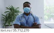 Portrait of african american male doctor wearing scrubs and face mask, crossing arms in hospital. Стоковое видео, агентство Wavebreak Media / Фотобанк Лори