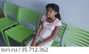 African american girl with arms crossed sitting on a chair at hospital. Стоковое видео, агентство Wavebreak Media / Фотобанк Лори
