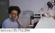 Mixed race hospital worker in reception talking on phone with doctors in backgrund. Стоковое видео, агентство Wavebreak Media / Фотобанк Лори