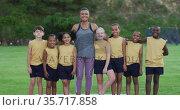 Portrait of mixed race female teacher and diverse group of schoolchildren smiling embracing outdoors. Стоковое видео, агентство Wavebreak Media / Фотобанк Лори