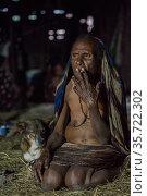 Dani tribe woman smoking. Budaya village, Suroba, Trikora Mountains, West Papua, Indonesia. March 2018. Стоковое фото, фотограф Pete Oxford / Nature Picture Library / Фотобанк Лори