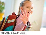 Lächelndes Kind mit Schulranzen geht zur Schule und winkt zum Abschied. Стоковое фото, фотограф Zoonar.com/Robert Kneschke / age Fotostock / Фотобанк Лори