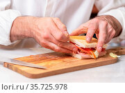 Chef finalizes the sandwich with ham and salad on the wooden board. Стоковое фото, фотограф Zoonar.com/DAVID HERRAEZ CALZADA / easy Fotostock / Фотобанк Лори