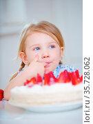 Mädchen kostet heimlich Sahne von einer Erdbeertorte in der Küche. Стоковое фото, фотограф Zoonar.com/Robert Kneschke / age Fotostock / Фотобанк Лори