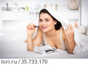 Sexy woman in nightdress relaxing and eating chocolate in bed. Стоковое фото, фотограф Яков Филимонов / Фотобанк Лори