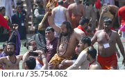 Kumbh Mela Haridwar India. Slowmotion shot of Sadhus or Saints of Akharas taking bath in Holy Water of River Ganges. Worship with Gadha a religious ornament.. Appleprores 422 Cinetone. Редакционное видео, видеограф Devendra Rawat / Фотобанк Лори