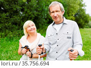 Paar Senioren beim Wandern mit Wanderstöcken im Feld im Sommer. Стоковое фото, фотограф Zoonar.com/Robert Kneschke / age Fotostock / Фотобанк Лори