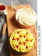 Delicious mini tarts with nuts and custard on wooden cutting board. Assortment of delicious and colorful dessert, lemon curd tart, cream chocolate tart made by chef. Стоковое фото, фотограф Nataliia Zhekova / Фотобанк Лори