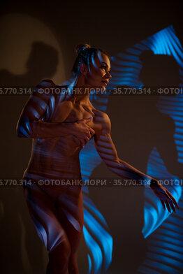 Nude woman standing in dark studio with neon light