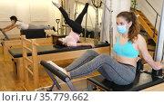 Gym woman protective mask pilates stretching sport in reformer bed. Стоковое видео, видеограф Яков Филимонов / Фотобанк Лори