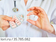 Ärztin hält eine einzelne Tablette und eine Blisterverpackung als... Стоковое фото, фотограф Zoonar.com/Robert Kneschke / age Fotostock / Фотобанк Лори