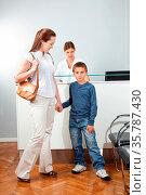Mutter mit Kind an der Hand steht an einer Theke. Стоковое фото, фотограф Zoonar.com/Robert Kneschke / age Fotostock / Фотобанк Лори