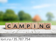 Camping word on a wooden cube sign with a blurry background of a ... Стоковое фото, фотограф Zoonar.com/Polarpx / age Fotostock / Фотобанк Лори