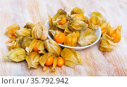 Closeup of yellow ripe physalis fruit on wooden table. Fruits and vegetables, vegetarian and healthy eating. Стоковое фото, фотограф Яков Филимонов / Фотобанк Лори
