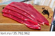 Sliced pieces of raw beef tenderloin on wooden cutting board. Стоковое фото, фотограф Яков Филимонов / Фотобанк Лори