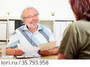 Freundlicher Berater mit Akte in einem Kundengespräch. Стоковое фото, фотограф Zoonar.com/Robert Kneschke / age Fotostock / Фотобанк Лори