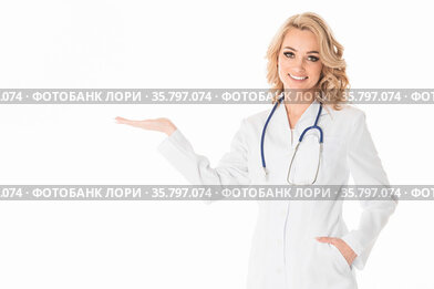Smiling female doctor in white coat pointing with hand palm at empty...