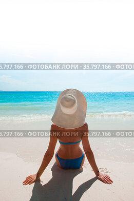 Woman in bikini and sunhat sitting on beach and looking at sea