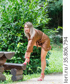 Young woman is tying high-heels shoes in park looking at camera slight... Стоковое фото, фотограф Emil Pozar / age Fotostock / Фотобанк Лори