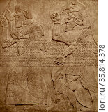Bas relief from Nimrud: Bearers of tribute in the form of apes from distant lands, as an offering to the Assyrian ruler. Редакционное фото, агентство World History Archive / Фотобанк Лори