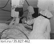 Nurse with patient at a Farm Security Administration (FSA) camp for migratory agricultural workers at Farmersville. 19380101. Редакционное фото, агентство World History Archive / Фотобанк Лори