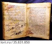 Open replica book of Biruni's astronomical encyclopaedia 'Kitab at-Qanun al-Mas'udi', showing planetary motions. Редакционное фото, агентство World History Archive / Фотобанк Лори