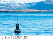 Buoy silhouette in the blue ocean with mountains in the background. Стоковое фото, фотограф Zoonar.com/Kasper Nymann / age Fotostock / Фотобанк Лори