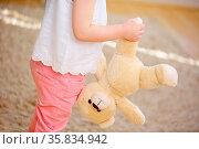 Kind trägt ein weiches Kuscheltier kopfüber am Bein. Стоковое фото, фотограф Zoonar.com/Robert Kneschke / age Fotostock / Фотобанк Лори