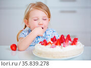 Kind probiert heimlich Sahne von einem frischen Erdbeerkuchen in ... Стоковое фото, фотограф Zoonar.com/Robert Kneschke / age Fotostock / Фотобанк Лори