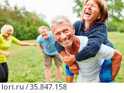 Vitale Senioren spielen zusammen im Sommer im Park und reiten Huckepack. Стоковое фото, фотограф Zoonar.com/Robert Kneschke / age Fotostock / Фотобанк Лори