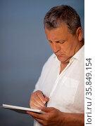 Waist Up of Mature Man Wearing White Shirt Using Pen on Handheld ... Стоковое фото, фотограф Zoonar.com/Danil Roudenko / age Fotostock / Фотобанк Лори