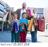 young parents with two children posing with many shopping bags on the street. Стоковое фото, фотограф Татьяна Яцевич / Фотобанк Лори