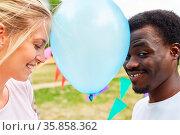 Mann und Frau beim Luftballontanz im Sommer als Spiel auf einer Party. Стоковое фото, фотограф Zoonar.com/Robert Kneschke / age Fotostock / Фотобанк Лори