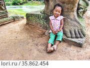 Portrait of a cute child at Preah Khan Temple. Siem Reap. Cambodia. Редакционное фото, фотограф Marco Brivio / age Fotostock / Фотобанк Лори
