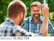 Mann als glücklicher Aktivist im Ehrenamt zusammen mit einem weiteren... Стоковое фото, фотограф Zoonar.com/Robert Kneschke / age Fotostock / Фотобанк Лори